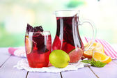 Red basil lemonade in jug and glass, on wooden table, on bright background — Stock Photo