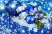 композиция с рождественские шары, подарочной коробке и снег на цветной деревянный фон — Стоковое фото