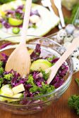 Fresh vegetable salad in bowl and plate on napkin on wooden table close-up — Stock Photo