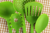 Plastic kitchen utensils on fabric background — Stock Photo
