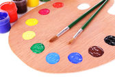 Wooden art palette with paint and brushes close-up — Stock Photo