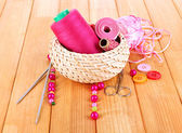 Handicraft supplies in basket on wooden table close-up — Stock Photo