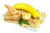Fresh and dried banana slices on wooden board, isolated on white — Stock Photo