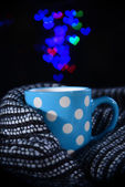 Cup of coffee with plaid on dark background — Stock Photo