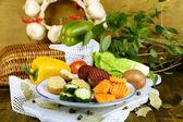 Schön geschnittene gemüse auf platte, auf hölzernen hintergrund — Stockfoto