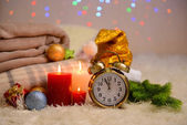 Composition with plaids, candles and Christmas decorations, on white carpet on bright background — Photo
