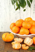 Ripe tangerines in bowl on table on wooden background — Stock Photo