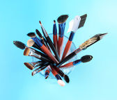 Makeup brushes in glass on bright background — Stock Photo