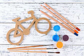 Decorative bicycle with drawing set on wooden background — Foto de Stock