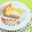 Slice of lemon cheesecake and sauce on plate, on wooden background — Stock Photo