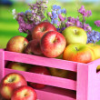 Juicy apples in box on white wooden table on natural background — Stock Photo