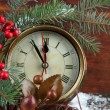 Clock with fir branches and Christmas decorations on table on wooden background — Stock Photo #37358799