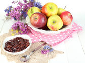 Juicy apples on plate on white wooden table — Stock Photo
