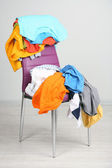 Heap of clothes on color chair, on gray background — Stock Photo