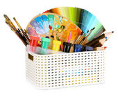 Plastic basket with art supplies isolated on white — Stock Photo