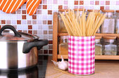 Pot on stove in kitchen on table on mosaic tiles background — Stock Photo