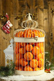 Tangerines in decorative cage with Christmas decor, on wooden background — 图库照片