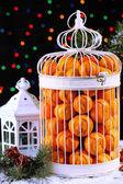 мандарины в декоративный клетка с рождественский декор, на фоне блестящей — Стоковое фото