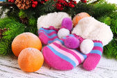 Striped mittens with fir branches and tangerines on wooden background — Stock Photo