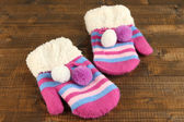 Striped mittens on wooden background — Stock Photo