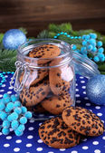 Delicious Christmas cookies in jar on table on wooden background — ストック写真