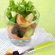 Fruit salad in glass, on wooden background — Stock Photo