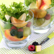 Stock Photo: Fruit salad in glasses, on wooden background