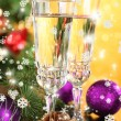 Composition with Christmas decorations and two champagne glasses, on bright background — Stock Photo #37360605