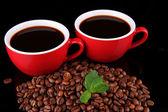 Cerrar rojos tazas de café y granos de café — Foto de Stock