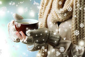 Female hands with hot drink, on light background — Stock Photo