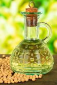 Soy beans and oil on table on bright background — Stock Photo