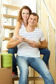 Mladý pár sedí na schodech s klíči do svého nového domova — Stock fotografie