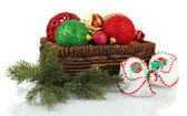 Christmas decorations in basket and shoes isolated on white — Stock Photo