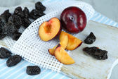 Fresh and dried plums on napkin, on wooden background — Stock Photo
