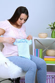 Young pregnant woman sitting on armchair and folding baby wear on wall background — Stock Photo
