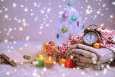 Composition with plaids, candles and Christmas decorations, on white carpet on bright background — Стоковое фото