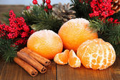 Christmas composition with frosted ripe tangerines on wooden background — Stock Photo