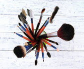 Makeup brushes in glass on wooden background — Stock Photo