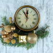 Clock with fir branches and Christmas decorations on wooden background — Stock Photo #37475649