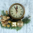 Clock with fir branches and Christmas decorations on wooden background — Stock Photo