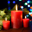 Composition with burning candles, fir tree and Christmas decorations on multicolor lights background — Stok Fotoğraf #37475655