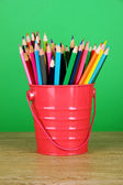 Colorful pencils in pail on table on green background — Stock Photo