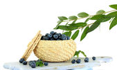 Blueberries in wooden basket on board on napkin isolated on white — Stock Photo