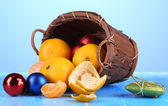 Christmas tangerines and Christmas toys in basket on blue background — Stock Photo