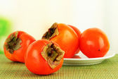 Ripe persimmons on plate on table on bright background — Stock Photo