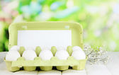 Eggs in paper tray on wooden table on natural background — Stock Photo