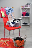Heap of clothes on color chair, on gray background — Foto Stock
