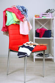 Heap of clothes on color chair, on gray background — Photo