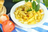 Ruddy fried potatoes on plate on tablecloth close-up — Stok fotoğraf