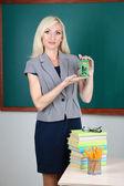Lärare nära tabell på tavlan bakgrund — Stockfoto